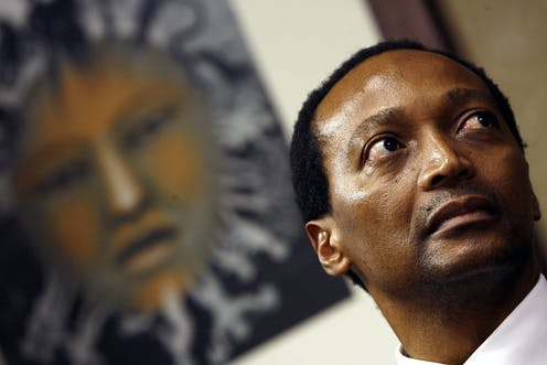 Portrait of a man listening intently, looking off to the side; behind him a poster of an African mask.