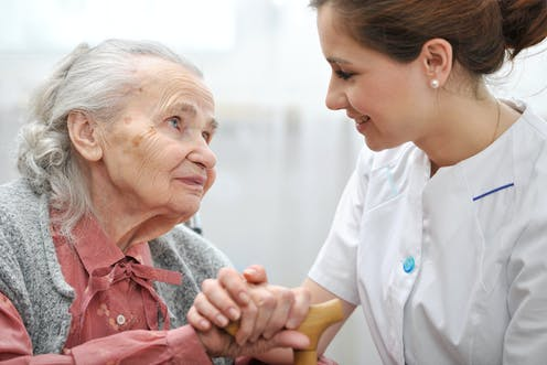 Elderly woman looking at young woman carer who is holding her hand.