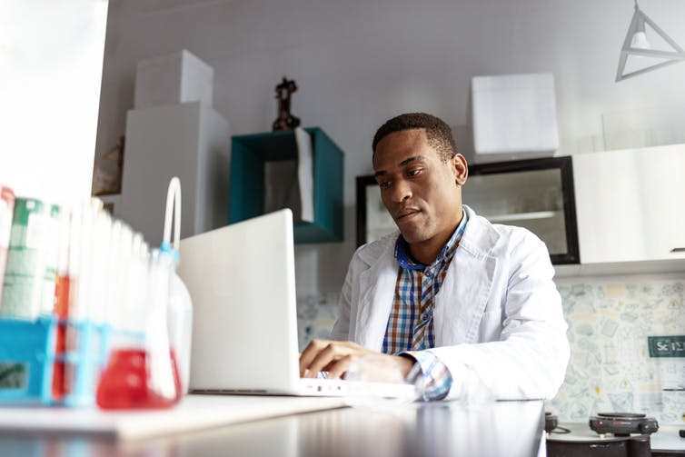 man in white coat in lab at laptop