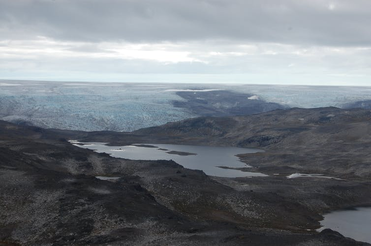A rocky barren landscape with a glacier in the distance