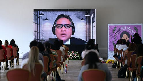 Backs of women sitting in chairs at a safe social distance watching a large screen. On the screen, a man speaks. Next to the screen is a banner reading '10 years without Manuela'