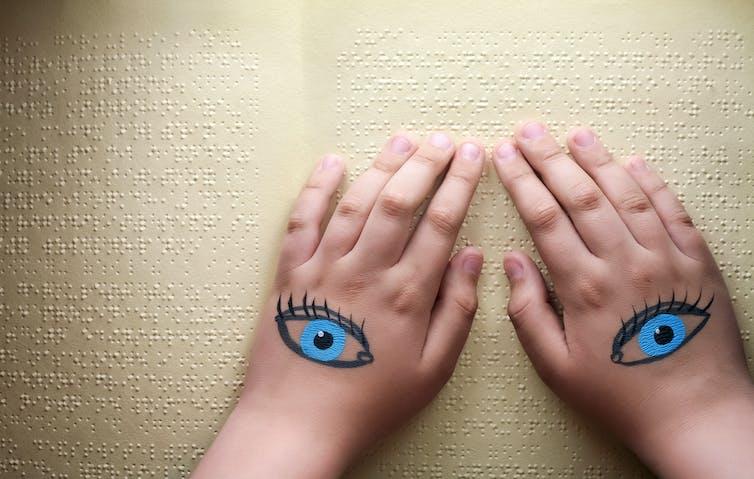 Unas manos con ojos pintados se deslizan sobre un texto en Braille.