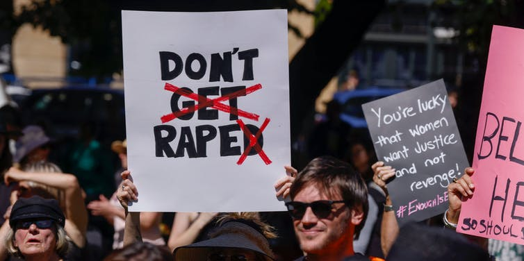 A woman at a rally holds up a protest sign.