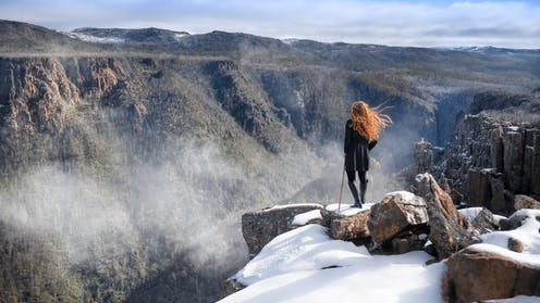 A woman stands on a snow capped ledge above a Tasmanian gully.
