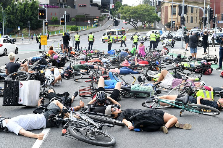 cyclists protest by staging a 'die-in' at a city intersection