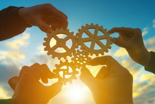 Four hands holding shapes of machine cogs fitting together