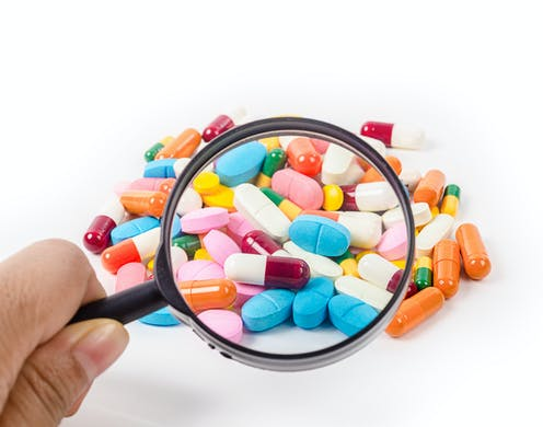 Lupa sobre un montón de pastillas de colores.