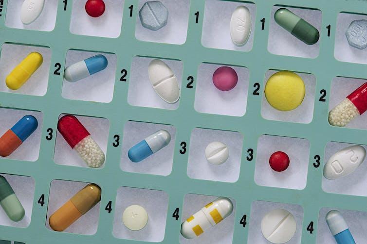 Pastillas de colores diversos en un pastillero cuadriculado y numerado.