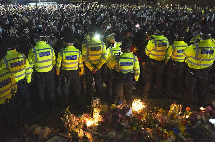 Police line up against protestors in Clapham, London.