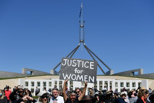 """March4Justice protestors outside parliament house, one holding a sign which reads """"Justice for Women"""""""