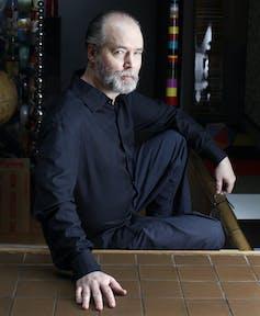 Photo of author Douglas Coupland sitting on steps.