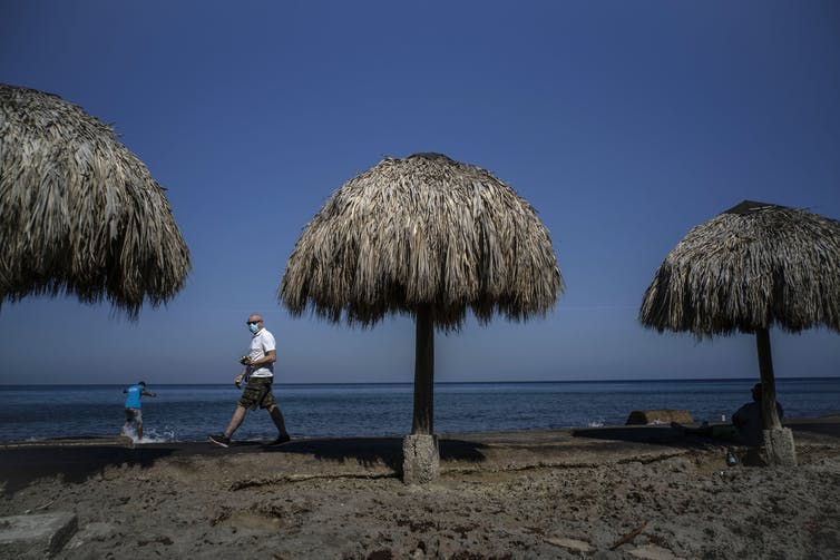 A man walks among beach huts wearing a mask.