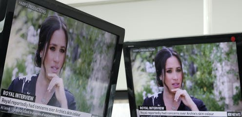 Meghan Markle is seen on two TV screens.