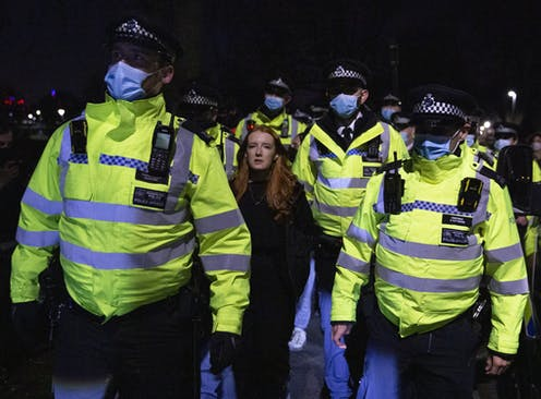A protester is flanked by five police officers in Clapham.