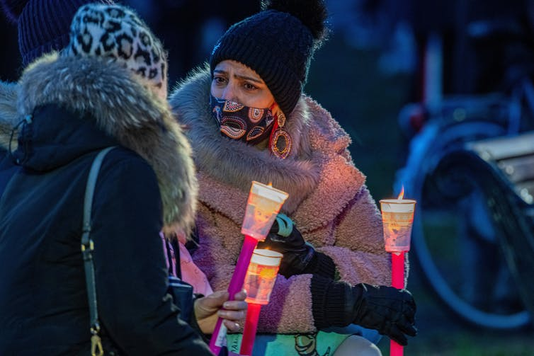 Attendees at the vigil for Sarah Everard talk as they hold torches fashioned out of disposable cups.