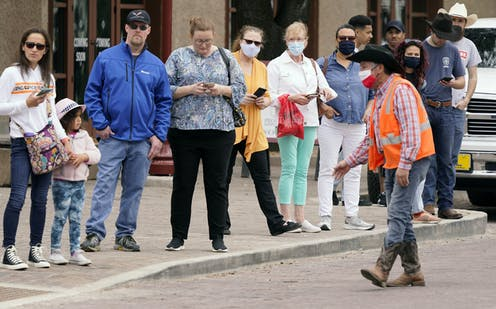 People stand on the curb very close to one another, some wearing masks, some not, as a man wearing a cowboy hat motions to them