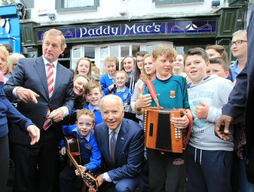 Joe Biden kneels outside Paddy Mac's bar in Ballina, County Mayo durng a vice-presidential visit to Ireland in 2016.