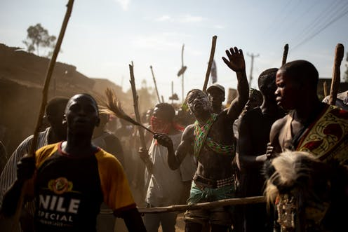 A throng of men in a village holding sticks with a young man in the middle of them, wearing animal skins, his face covered in clay.