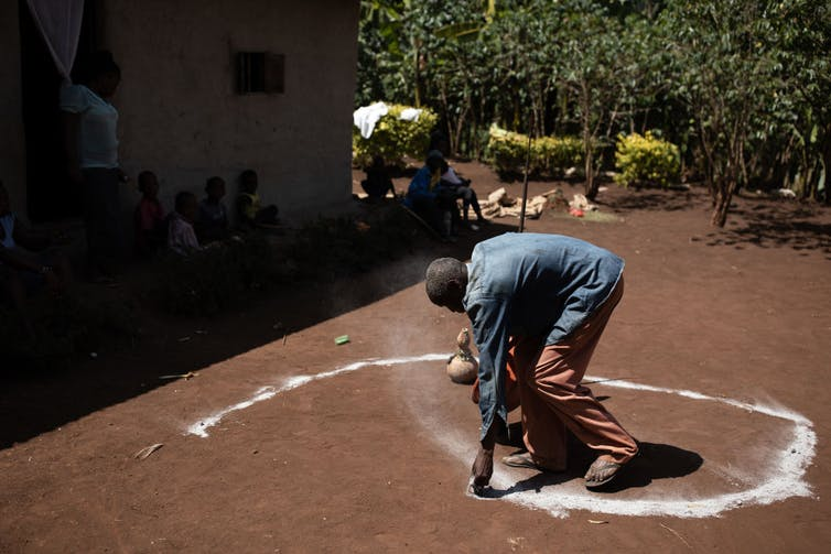 An elderly man is bent over, using white chalk to form a spiral shape on the dirt ground.