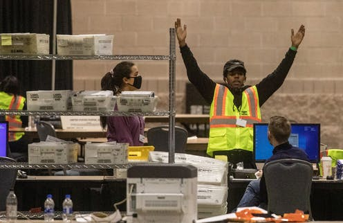 An election worker surrounded by boxes of mail-in ballots inside a convention center after Election Day