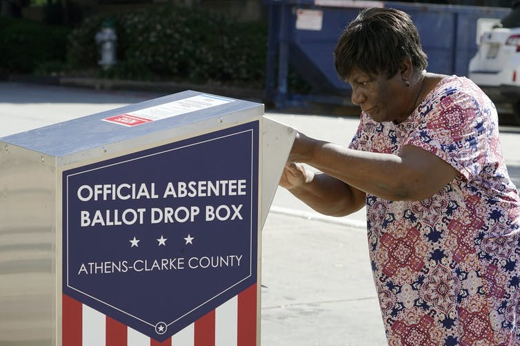 A woman dropping off her ballot in a drop box in Athens, Georgia