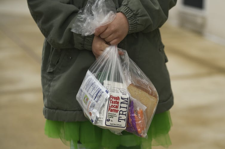 Child carries lunch in plastic bag