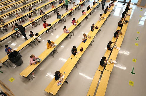 Students social distance in school cafeteria