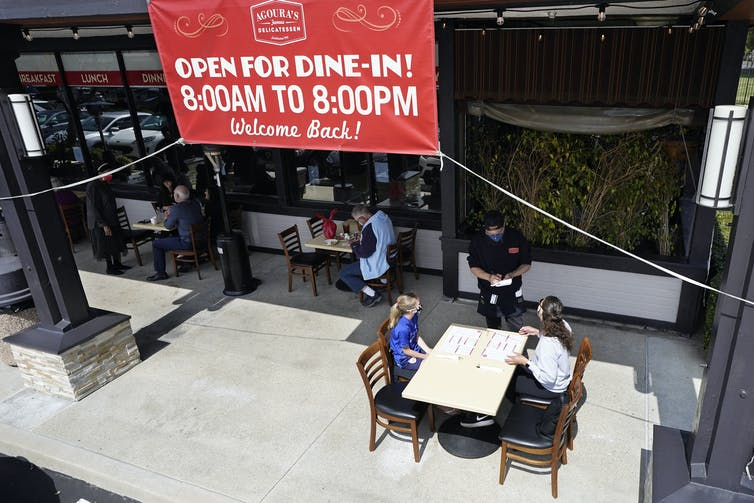 A sign over a restaurant in Los Angeles says 'Open for dine-in! 8:00AM to 8:00PM. Welcome Back!' above several diners at tables outside.