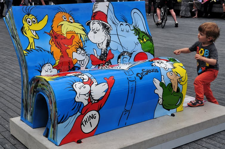A child approaches a Dr. Seuss BookBench sculpture