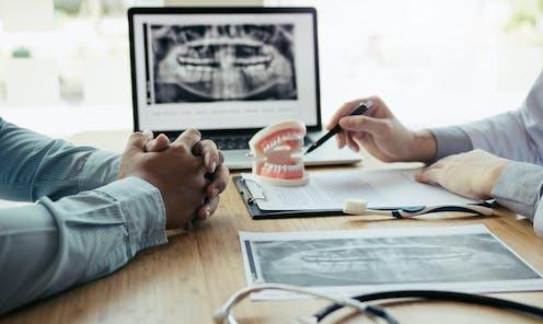 Consulta de un odontólogo, que señala una dentadura falsa.