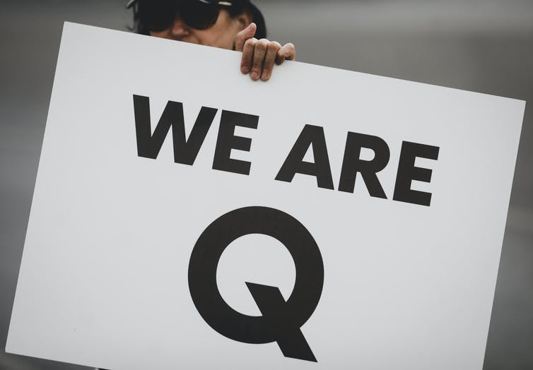 Woman holding up a sign that reads 'We are Q'