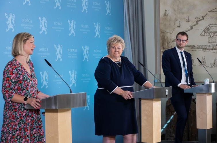 Two women and a man stand on a stage at lecterns, at a safe social distance.