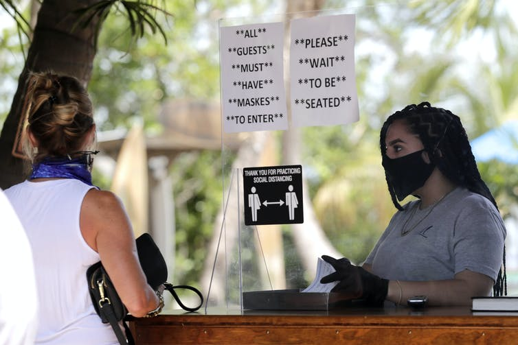 A woman worker wearing a mask waits for a customer whose face is turned away to order at a cafe.