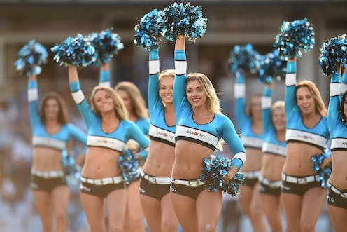 Cheerleaders in skimpy outfits with pom poms.