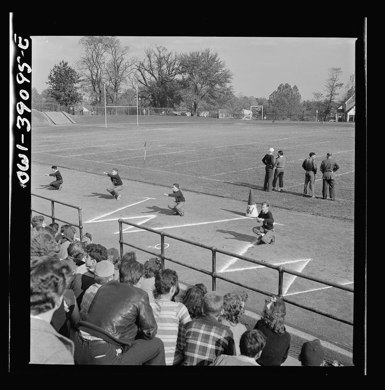 Black and white photo. Four boys squat in a cheer in front of bleachers.
