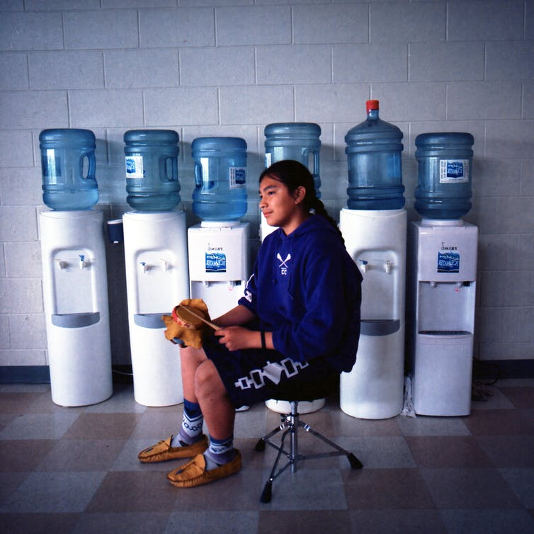 A young man with lacrosse stick in front of bottled water jugs.