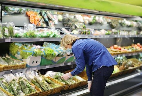 Una persona eligiendo verdura en una frutería.