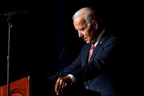 Joe Biden at a lectern with his head bowed