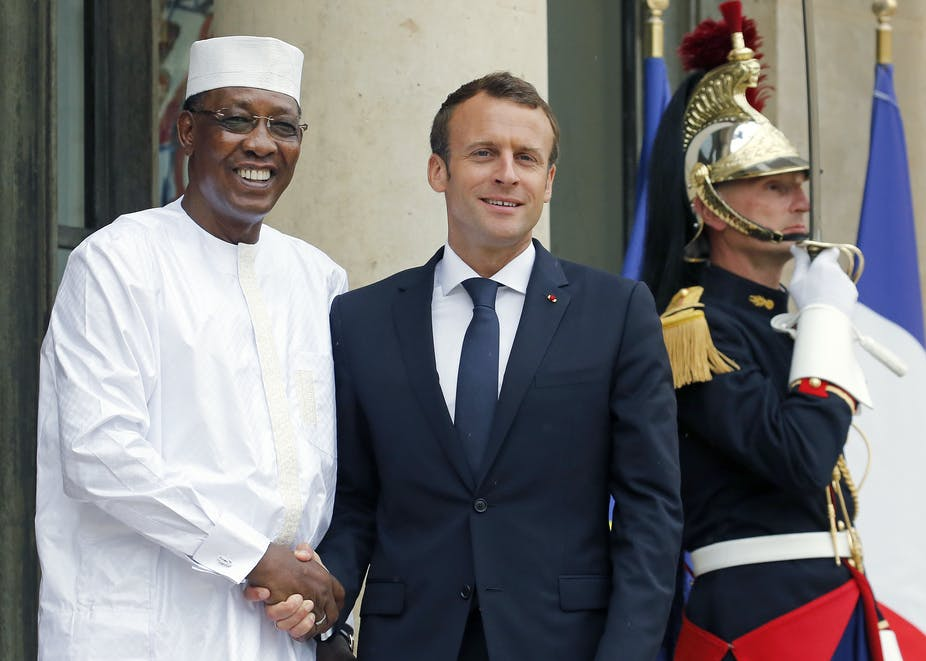 A man black in white Muslim garb greets a white man in a blue suit