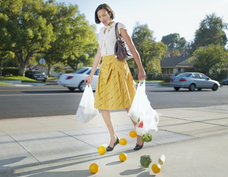 woman with fruit spilling out of ripped grocery bags