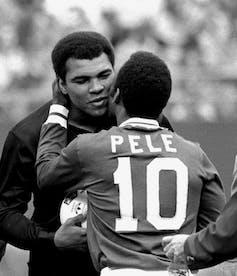 Two men embrace.