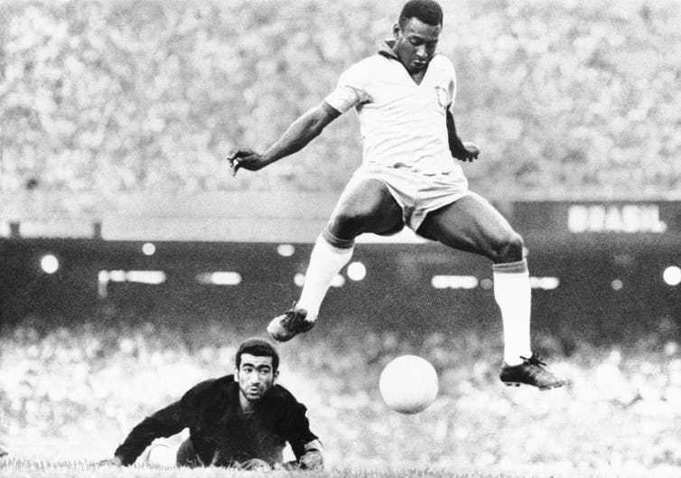 Soccer player is seen mid-air, ball between his feet.
