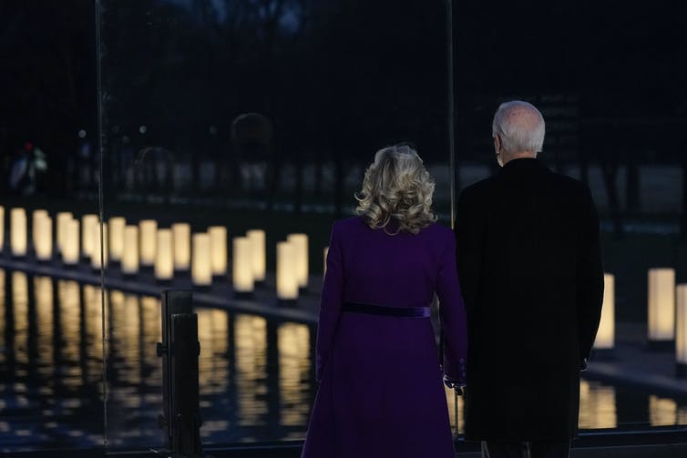 Joe and Jill Biden look out at lights during a COVID-19 memorial.