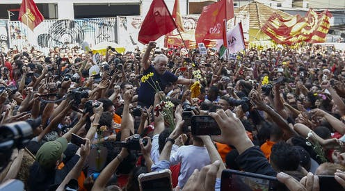 Crowd hoists Lula onto their shoulders, holding flowers and taking picture. Lula has a defiant fist raised.