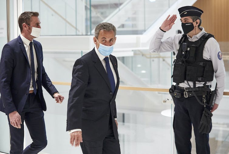 Sarkozy, wearing a face mask, walks through a glass building, trailed by another man in a suit. A police officer salutes.