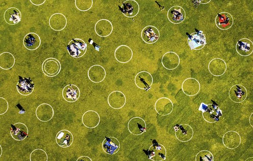 White social distancing circles painted on grass