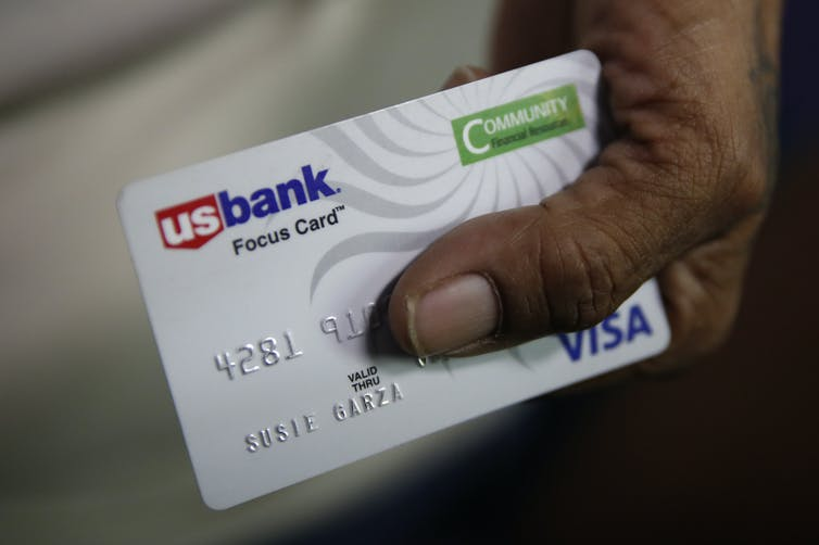 A hand holds a debit card used in the Stockton, California, basic income experiment.