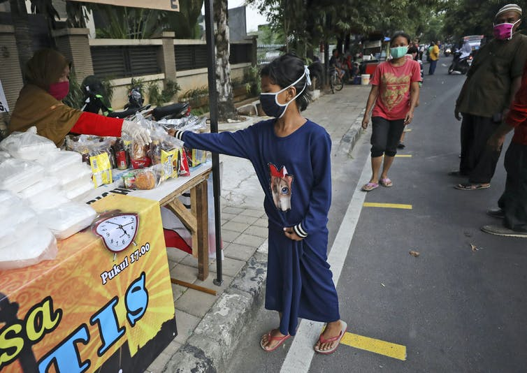 Girl in Indonesia wearing mask and reaching for food in a market stall.