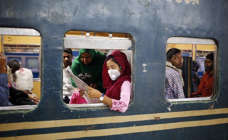 Girl reading newspaper in a crowded train in Balgladesh.