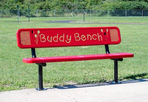 A red buddy bench in school field.